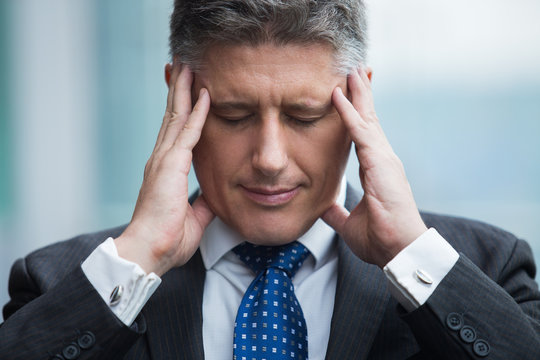 Portrait of stressed businessman touching his head