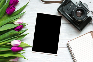 vintage retro camera with blank photo frame and purple tulip flowers with blank notebook
