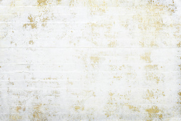 White grunge wall with gold layer in the backround