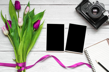 blank photo frames, vintage retro camera and purple tulip flowers with blank notebook