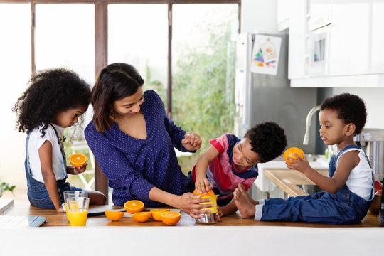 Une maman et ses enfants préparent du jus d'orange dans la cuisine