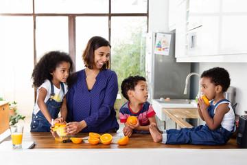 Des enfants font du jus d'orange avec leur mère