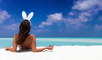 Frau mit Hasenohren und Ostereiern am tropischen Strand