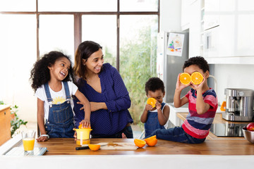 Famille qui joue dans la cuisine en préparant du jus d'orange