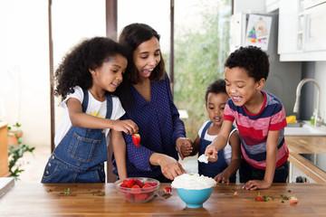 Famille qui mange des fraises et de la chantilly dans la cuisine