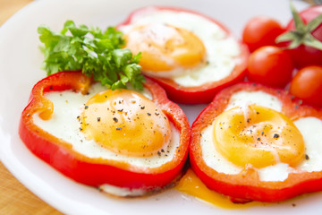 fried eggs in red peppers in a plate close-up.
