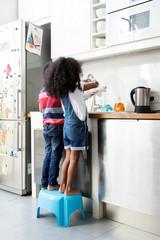 Un frère et une soeur font la vaisselle dans la cuisine vus de dos