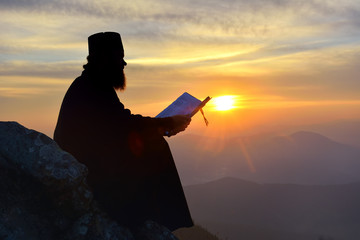 silhouette of priest reading in the sunset light, Romania
