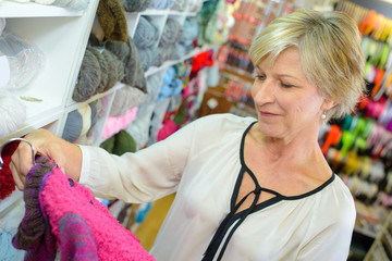 Woman looking appreciatively at knitted garment