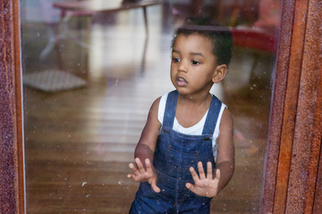 Un petit garçon regarde dehors par la fenêtre du salon