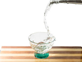Water falling into glass on cutting board from bottle