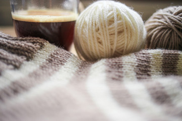 Beige and white yarn, beige-beige sock and black coffee are on the table. Wooden background. Hobbies