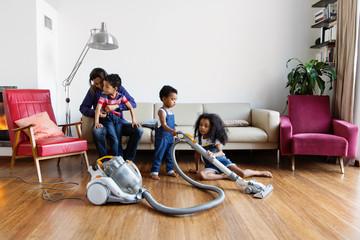 Une famille passe l'aspirateur dans le salon