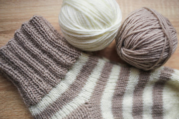 Beige and white yarn, Knitted striped beige-beige sock are on the table. Wooden background. Hobbies