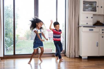 Un frère et une soeur dansent devant la fenêtre du salon
