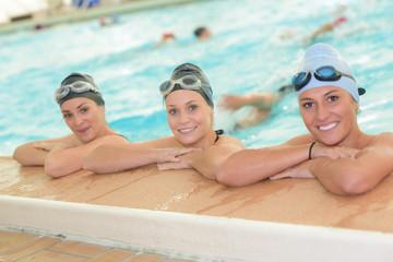 three swimmers posing