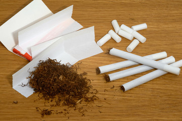 Homemade cigarettes, filters and tobacco paper on wooden background