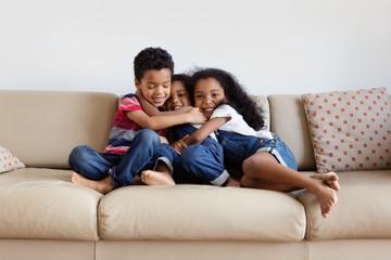 Trois enfants se font un câlin sur le canapé