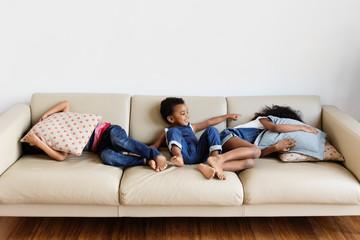 Trois enfants jouent à cache-cache sur le canapé