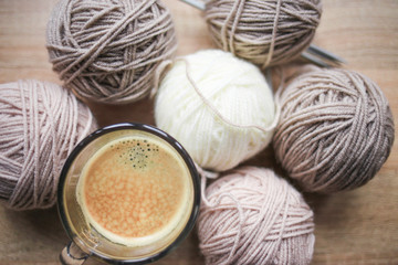Coffee, knitting needles, beige and white yarn are on the table. Wooden background. Hobbies