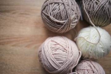 Knitting needles, beige and white yarn are on the table. Wooden background. Hobbies