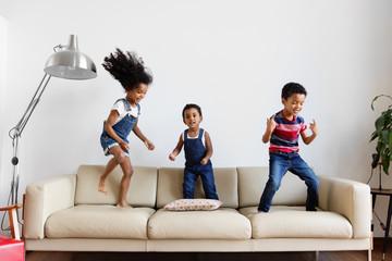 Trois enfants dansent sur le canapé du salon