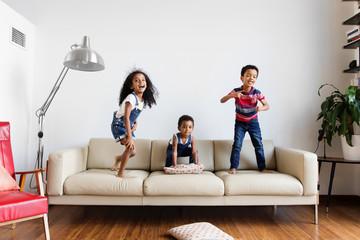 Trois enfants jouent et rient sur le canapé