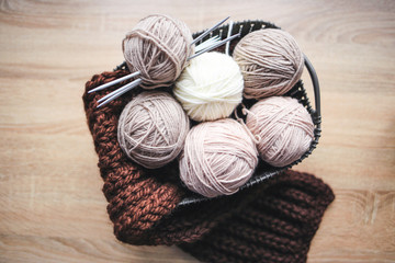 Beige yarn, knitting needles and a brown scarf are in the basket. Wooden background. Hobbies