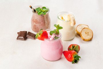Selection of classic milkshakes in small jars: chocolate, strawberry, banana. On a white wooden table, with tubes, copy space