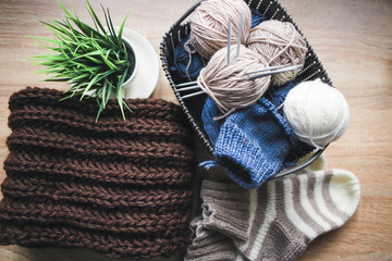Beige, white and blue yarn, knitting needles in the basket and a brown scarf. Striped beige-white knitted socks and a green plant in the pot. Wooden background. Knitting hobby