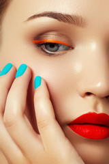Woman's face with vivid make-up and colorful nail polish