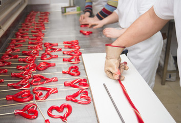 Lollipop making from melted hot sugar in traditional candy workshop