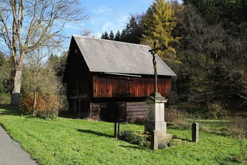 Old barn and cross in Bohemian Switzerland