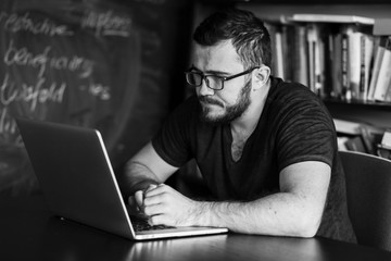 Man worn glasses. Software Engineer is sitting and working. He is looking into his laptop. Black and white photo.