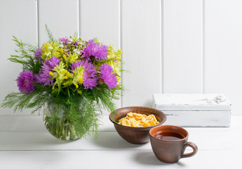Flowers bouquet in vase with cup tea and corn flakes