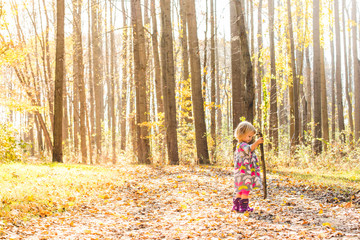 Preschool girl in forest holding stick