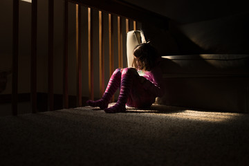 Girl sitting in darkness reading book