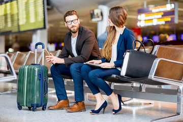 Elegant business couple sitting with phone and book at the waiting hall in the airport. Business travel concept
