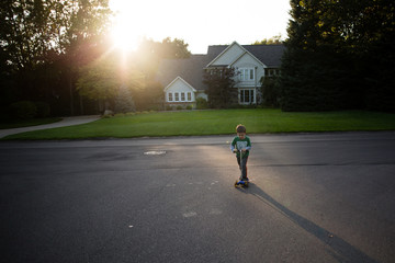 Boy playing on scooter in driveway