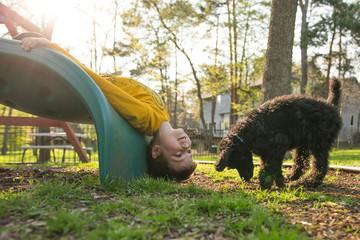 Boy with dog upside down on slide