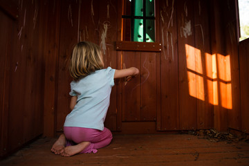 Girl drawing on playhouse walls with chalk