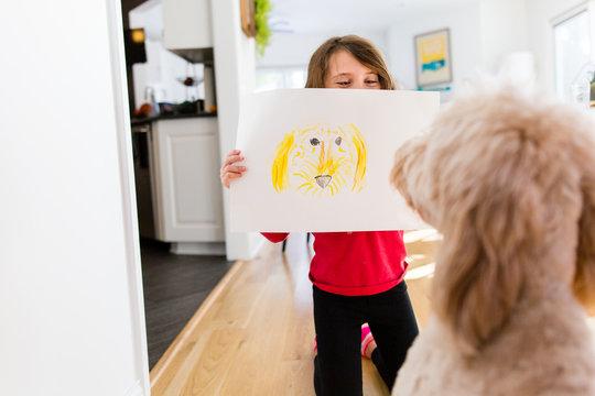 Girl showing crayon drawing to dog