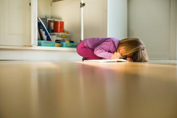 Preschool girl lying on floor drawing in drawing pad