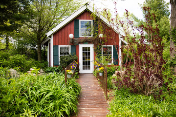 Wooden path in garden leading to cottage