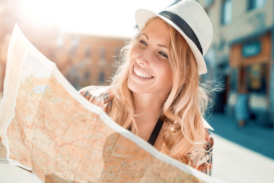 Happy young woman using a city map