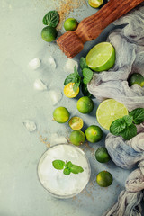 Ingredients for mojito cocktail, whole, sliced lime and mini limes, mint leaves, brown crystal sugar over gray stone texture background, gauze textile, bar muddler, glass of ice. Top view, space