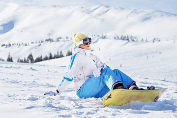 Young beautiful girl in white jacket, blue ski pants and googles on her head sitting with snowboard in the snowy mountains. Winter sports.