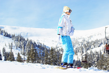 Young beautiful girl in white jacket, blue ski pants and googles on her head riding on snowboard in the snowy mountains. Winter sports.