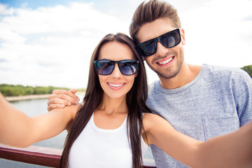 An image of young lovely couple having a walk taking a selfie against nature