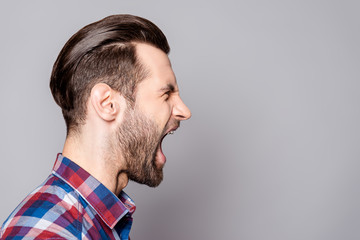A half-face portrait of a young bearded yelling man with fashionable haircut isolated against gray background